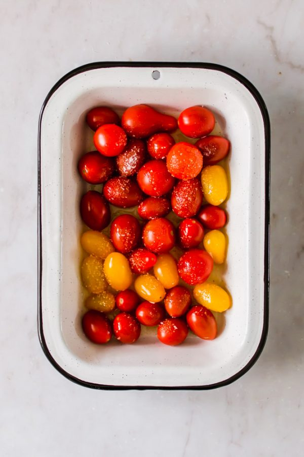 white baking dish with salted red and yellow cherry tomatoes