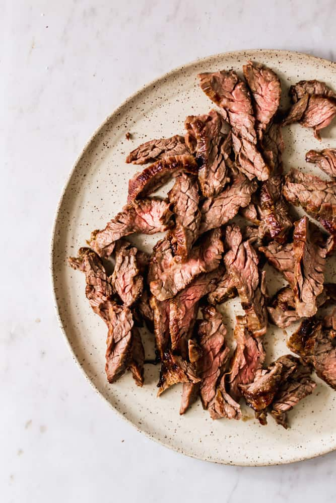 cooked strips of skirt steak on a beige plate