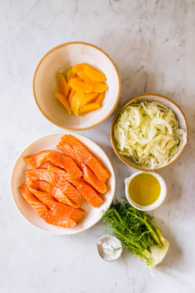 small white bowls filled with orange slices, shaved fennel, raw salmon, and oil