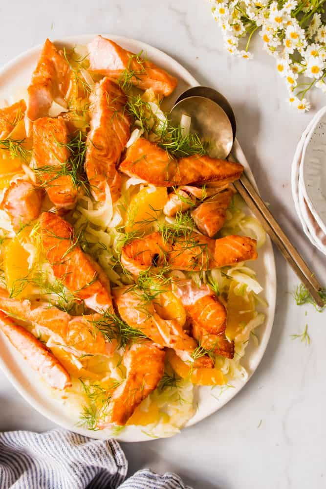 large white platter with spoons filled with shaved fennel, cooked salmon fillets, oranges, and topped with dill