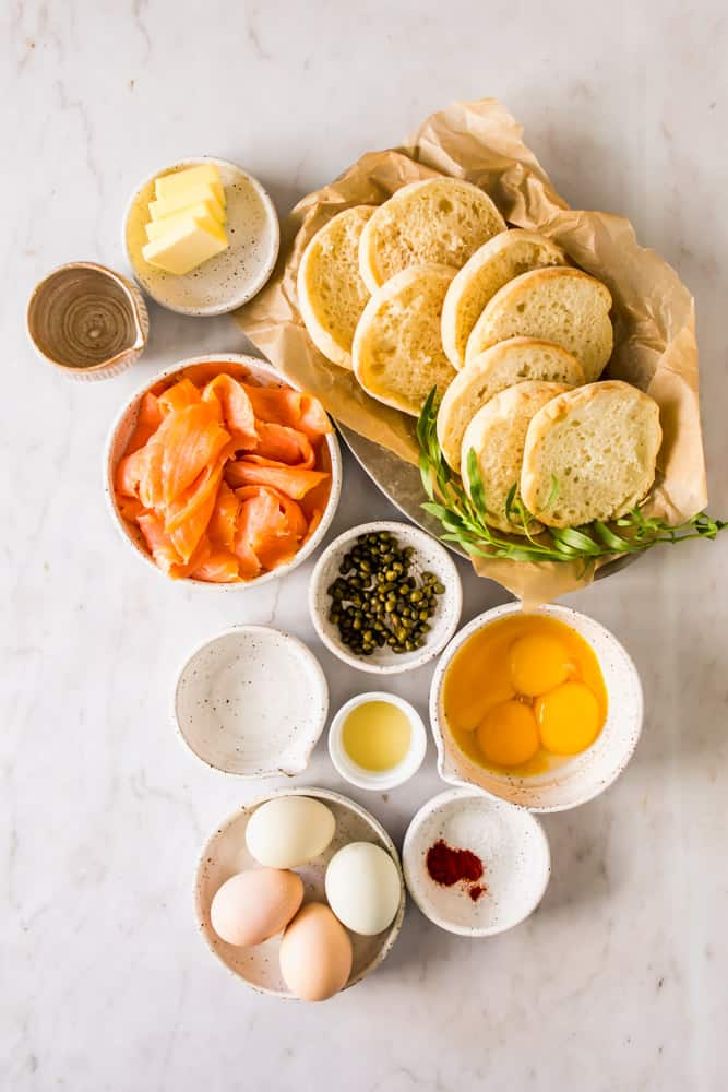 small white bowls with smoked salmon, capers, eggs, capers, and english muffins