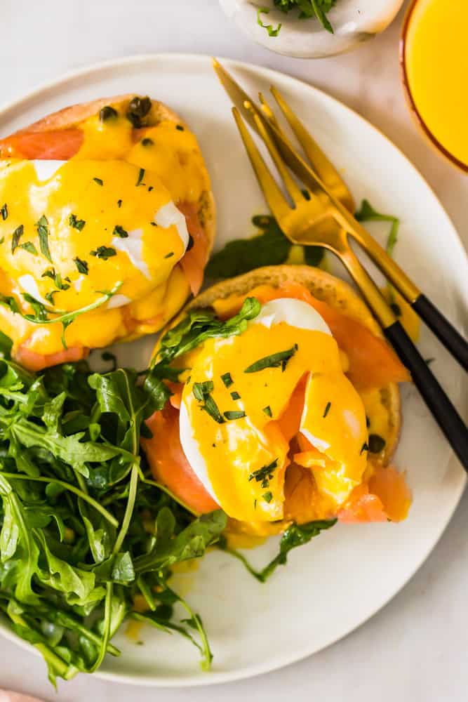 close up of eggs benedict on a white plate next to gold utensils and leafy greens