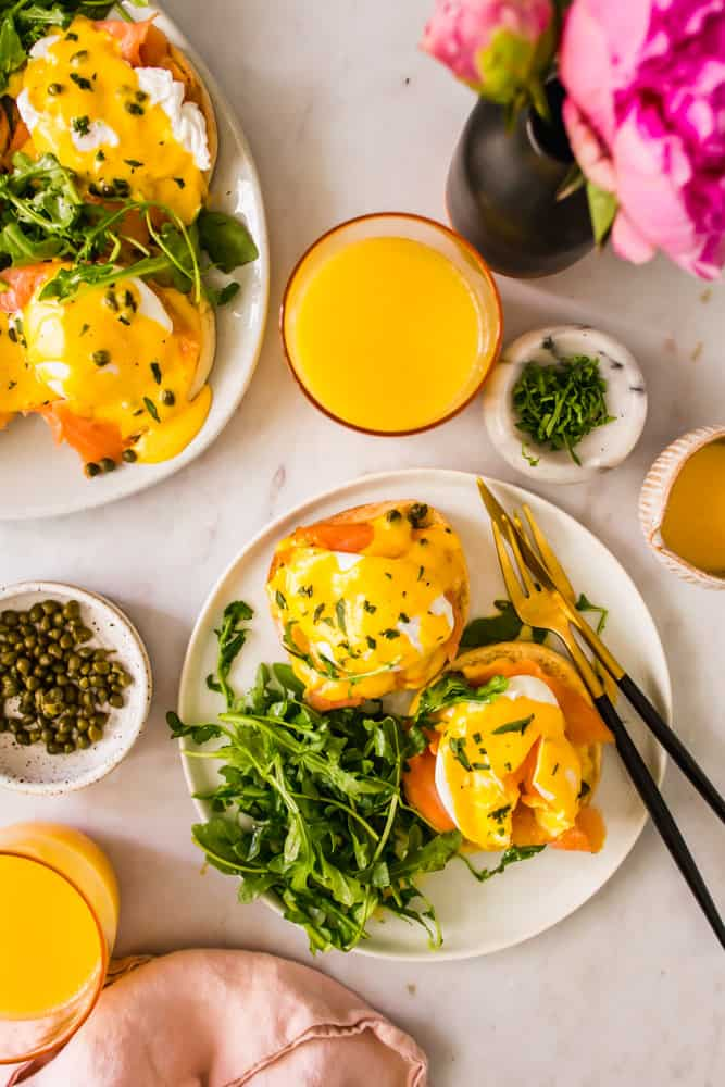 white plates with eggs benedict next to small bowls of capers, herbs, and orange juice