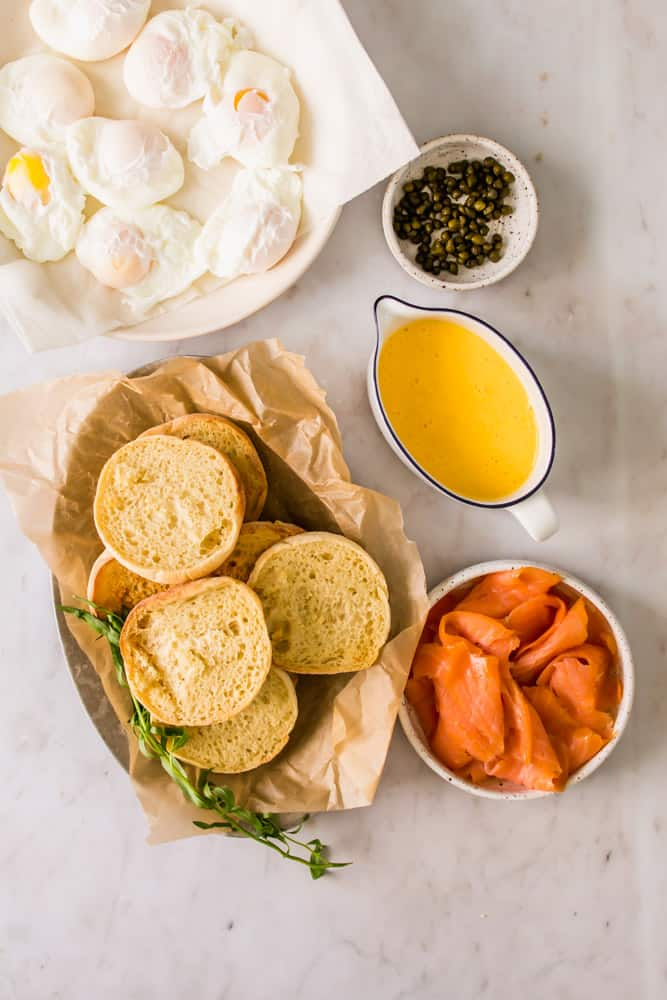 white bowls with toasted english muffins, smoked salmon, poached eggs, yellow hollandaise sauce, and capers