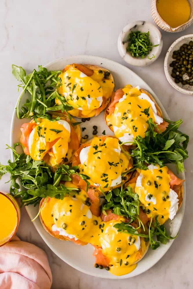 large white serving plate with eggs benedict and leafy greens