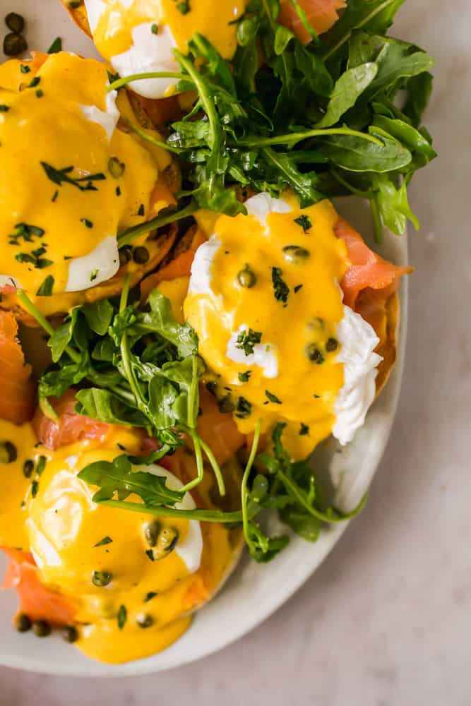 close up on eggs benedict with leafy greens, yellow hollandaise, and capers on top