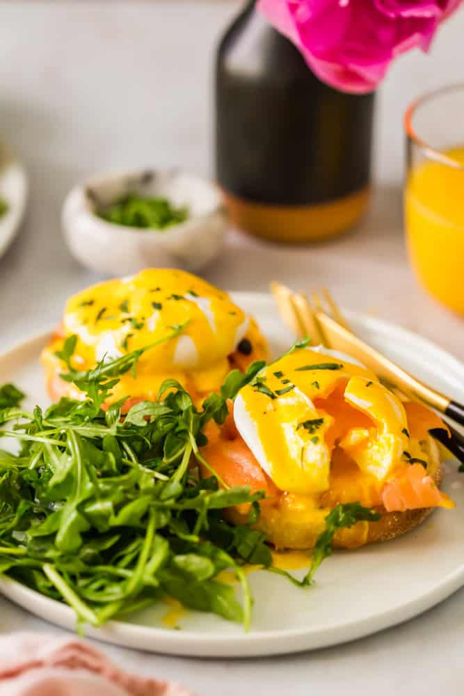 2 eggs benedict on a white plate next to leafy greens