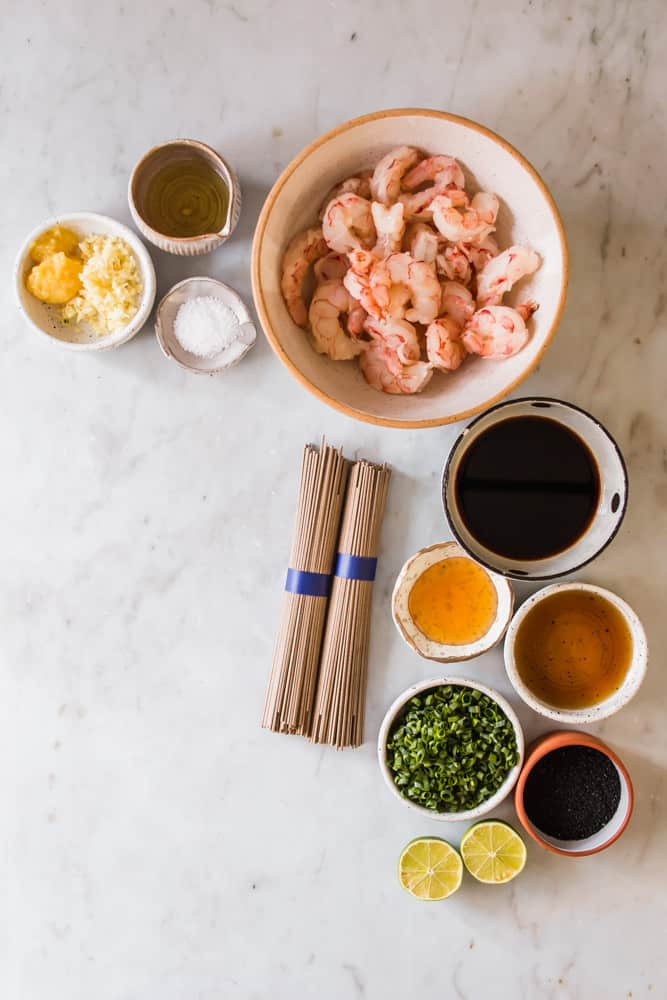 small white bowls filled with raw shrimp, oil, garlic, brown sauces, and green onions.