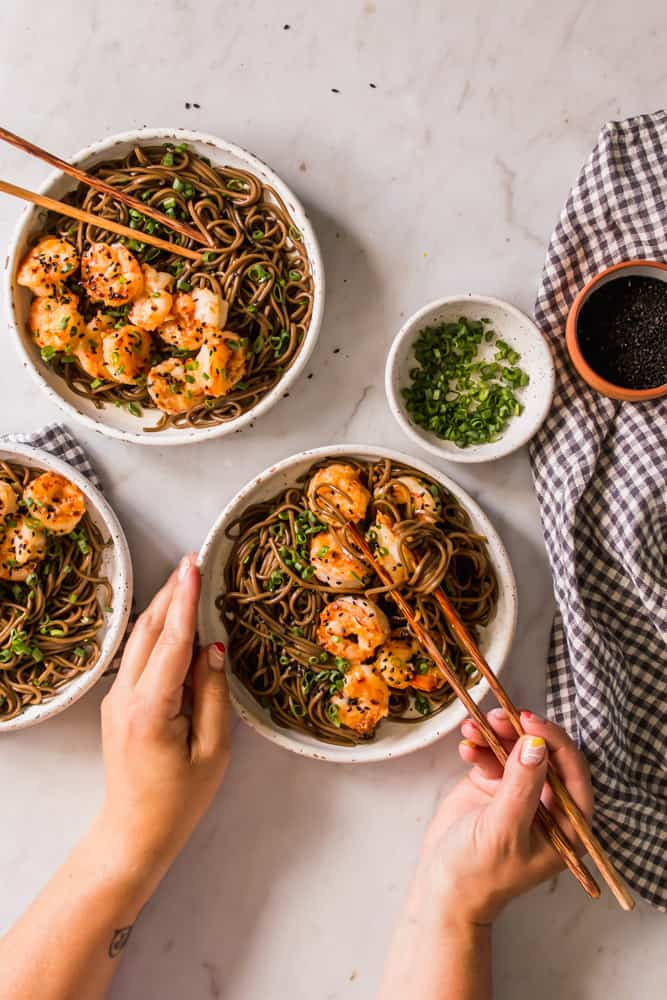 womans hands using wood chopsticks to eat brown noodles and cooked shrimp from a white bowl