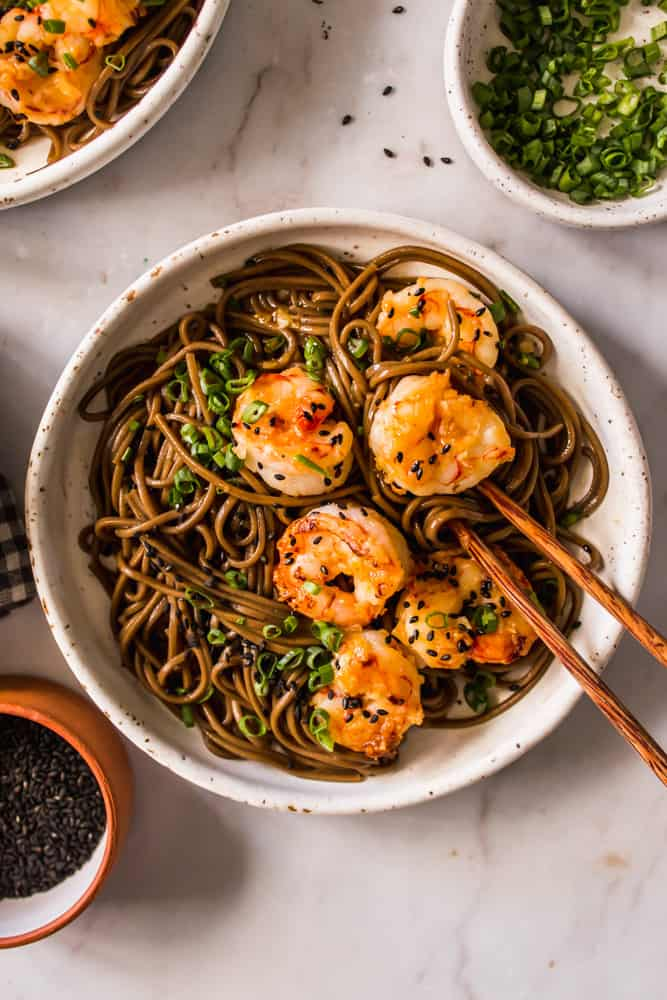 close up on cooked shrimp and brown noodles in a white bowl with wood chopsticks