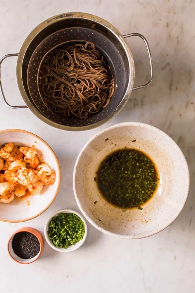 strainer with cooked brown noodles inside, next to white bowls filled with a brown sauce and cooked shrimp