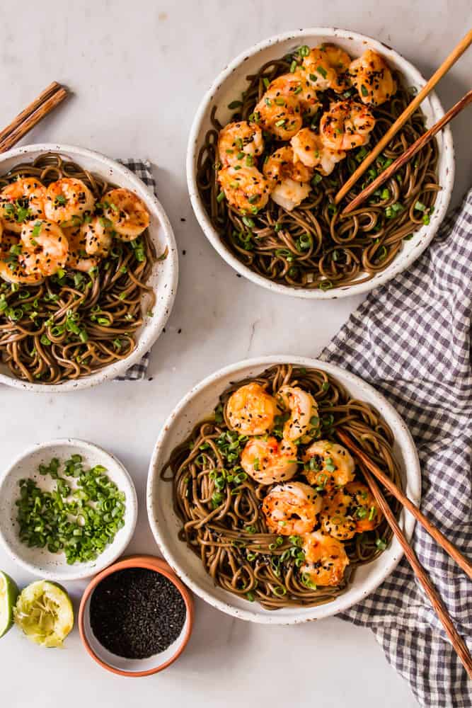 3 white bowls filled with cooked brown noodles, shrimp, and wood chopsticks