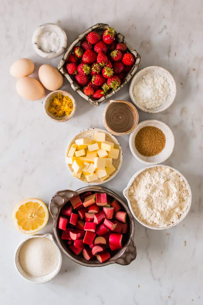 small white bowls filled with flour, butter, sugar, strawberries, and pieces of rhubarb