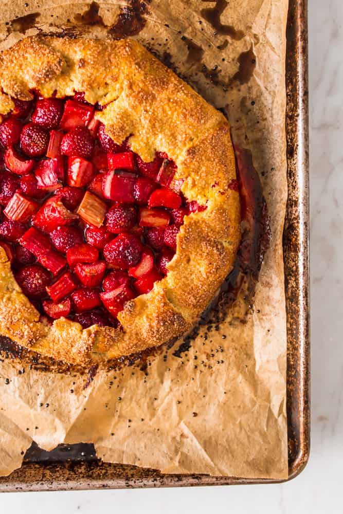 baked golden brown galette crust on a baking sheet with strawberries and rhubarb in the center