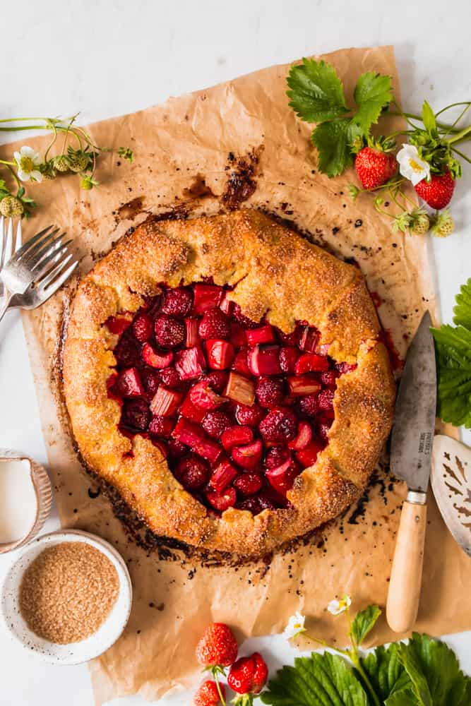 baked golden brown galette crust on a parchment paper with strawberries and rhubarb in the center