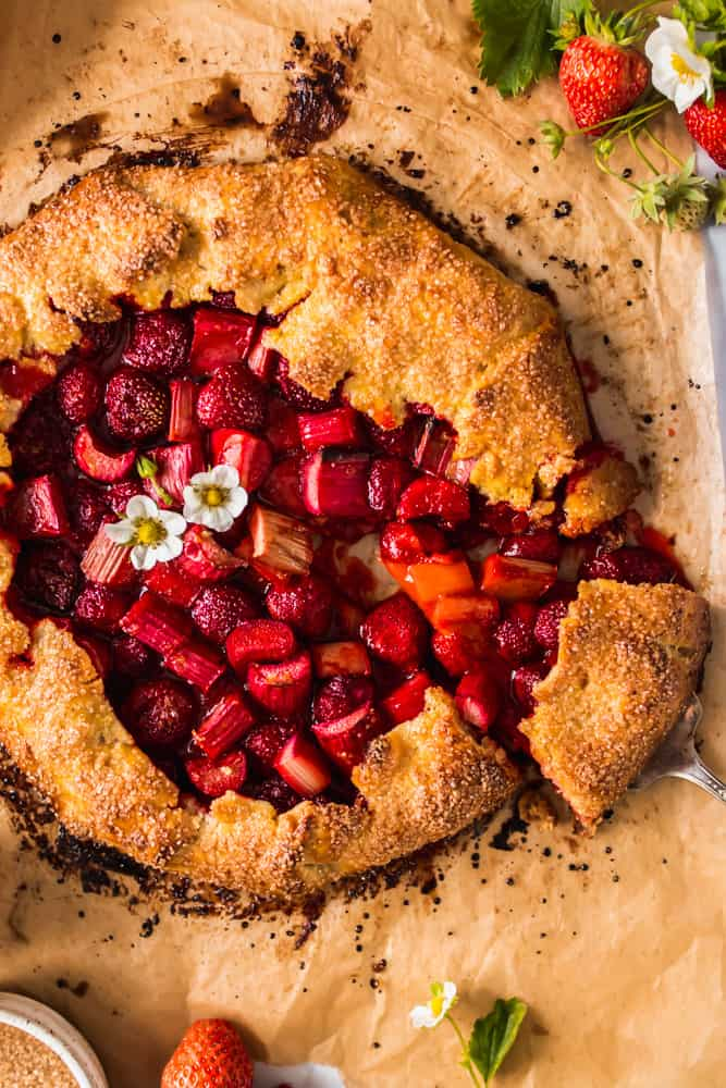 removing a slice of a red and golden brown strawberry and rhubarb galette from a piece of parchment paper