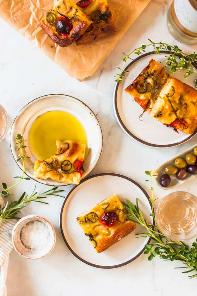small white plates holding slices of baked focaccia bread and oil