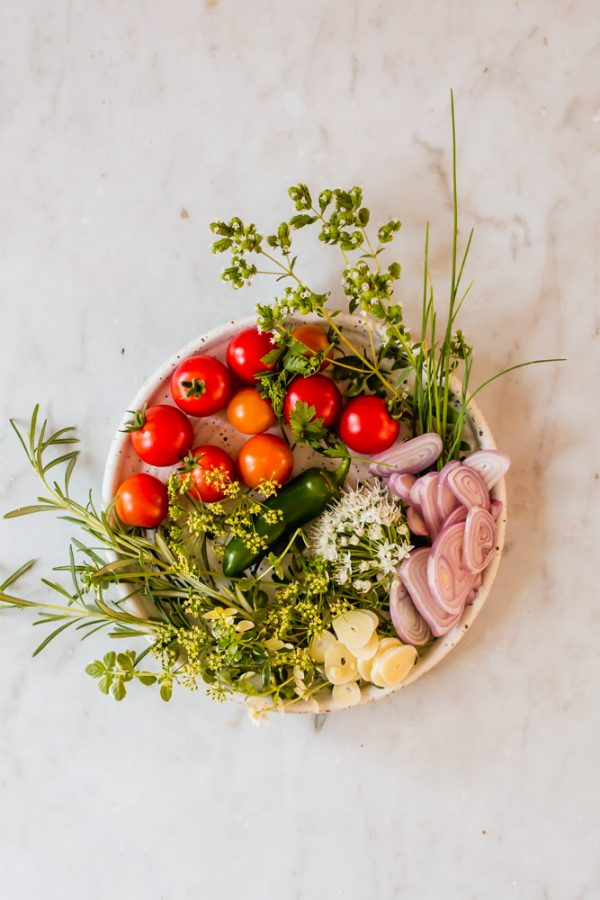 white bowl filled with vegetables and herbs