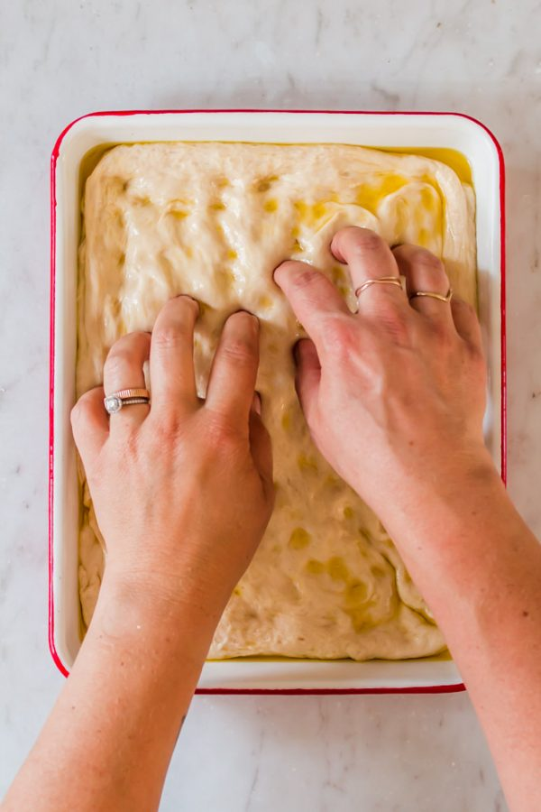 womans hands poking dimples into bread dough