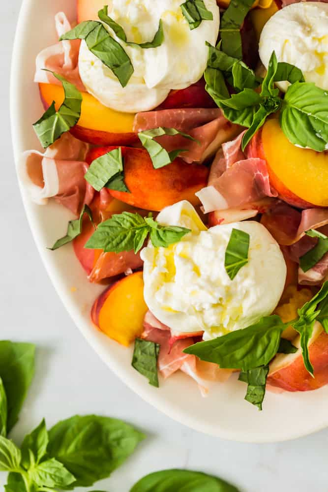 close up on a peach and prosciutto salad on a white platter topped with white burrata cheese and green herbs