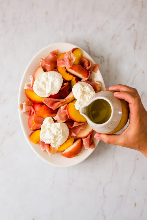 pouring oil over peaches, prosciutto, and cheese on a white platter