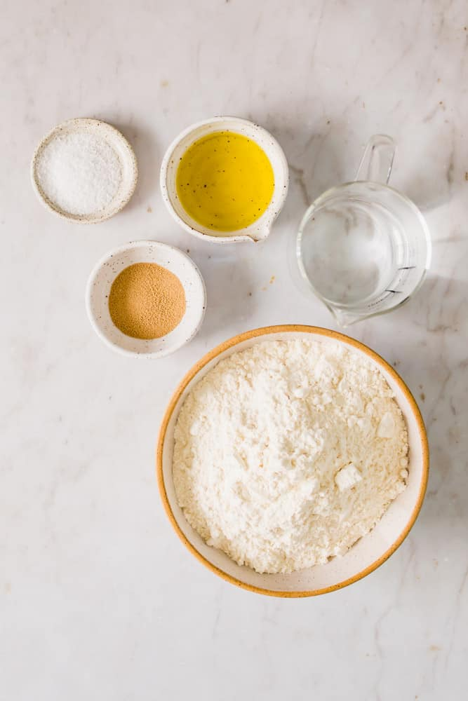 individual white bowls with flour, yeast, salt, and oil