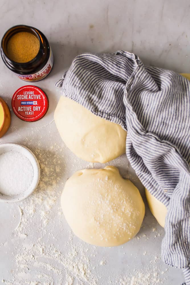 balls of bread dough next to a striped dish towel and a bottle of yeast