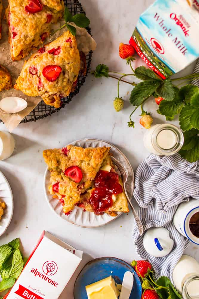 sliced strawberry scone with butter and red jam on a white plate next to a wire rack with more strawberry scones