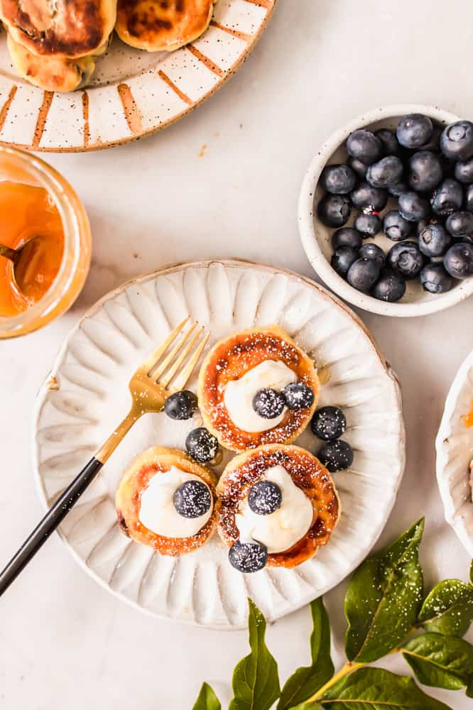 close up on 3 small pancakes topped with cream and blueberries on a white plate