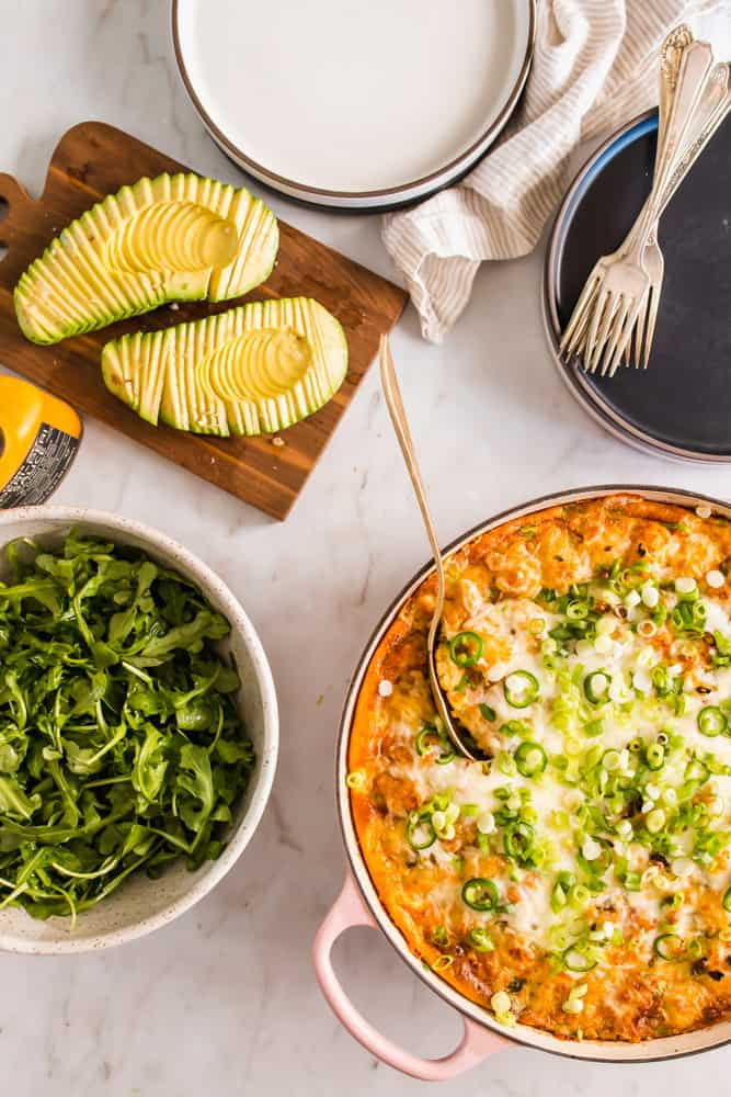 large skillet with baked eggs and cheese next to sliced avocado, greens, and plates