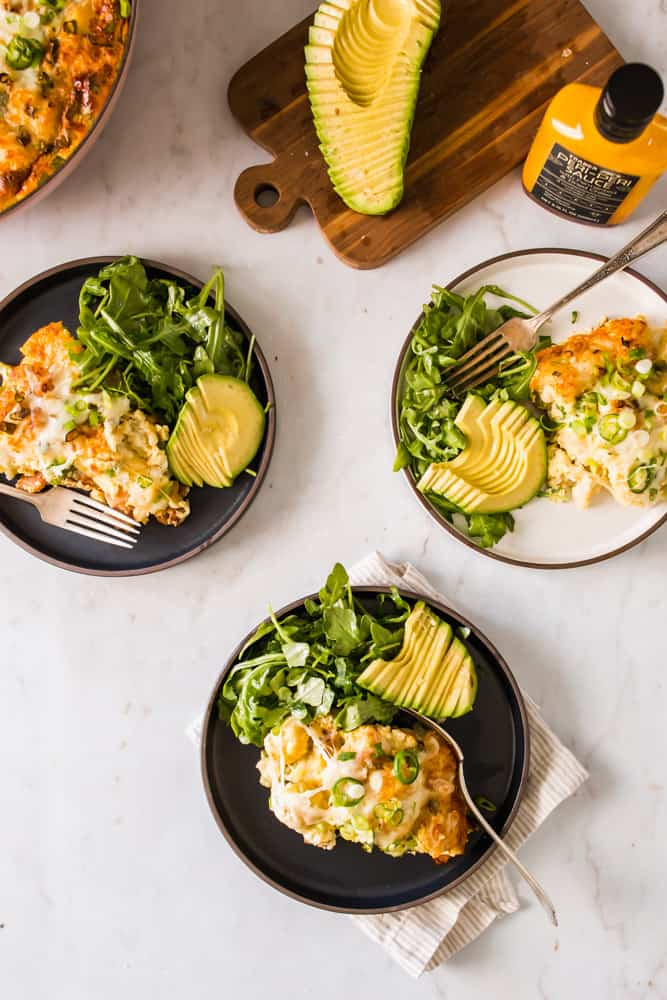 individual plates with scoops of an egg casserole, arugula, and avocado