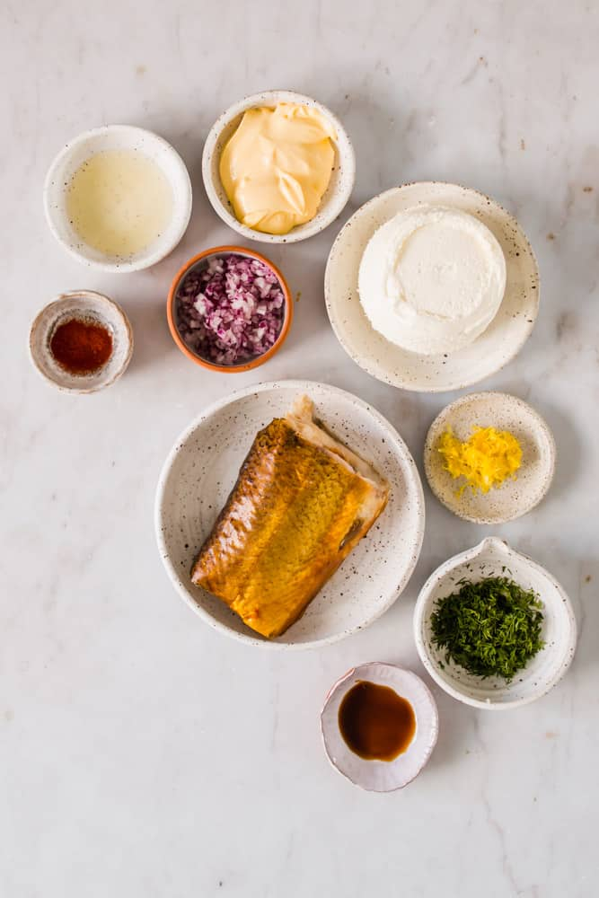 individual white bowls holding smoked fish, cream cheese, vegetables, mayonnaise, and seasonings