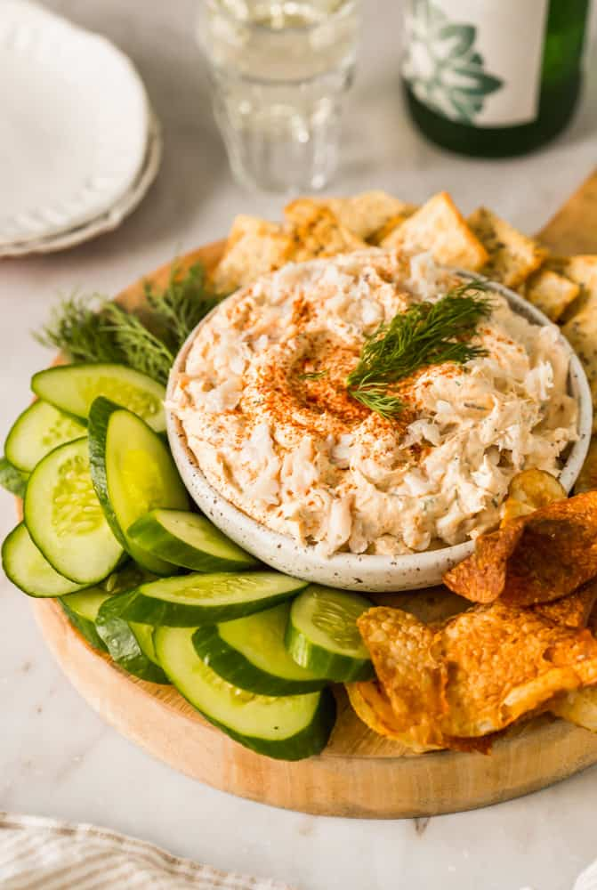 white creamy fish dip in a bowl surrounded by cucumbers and crackers