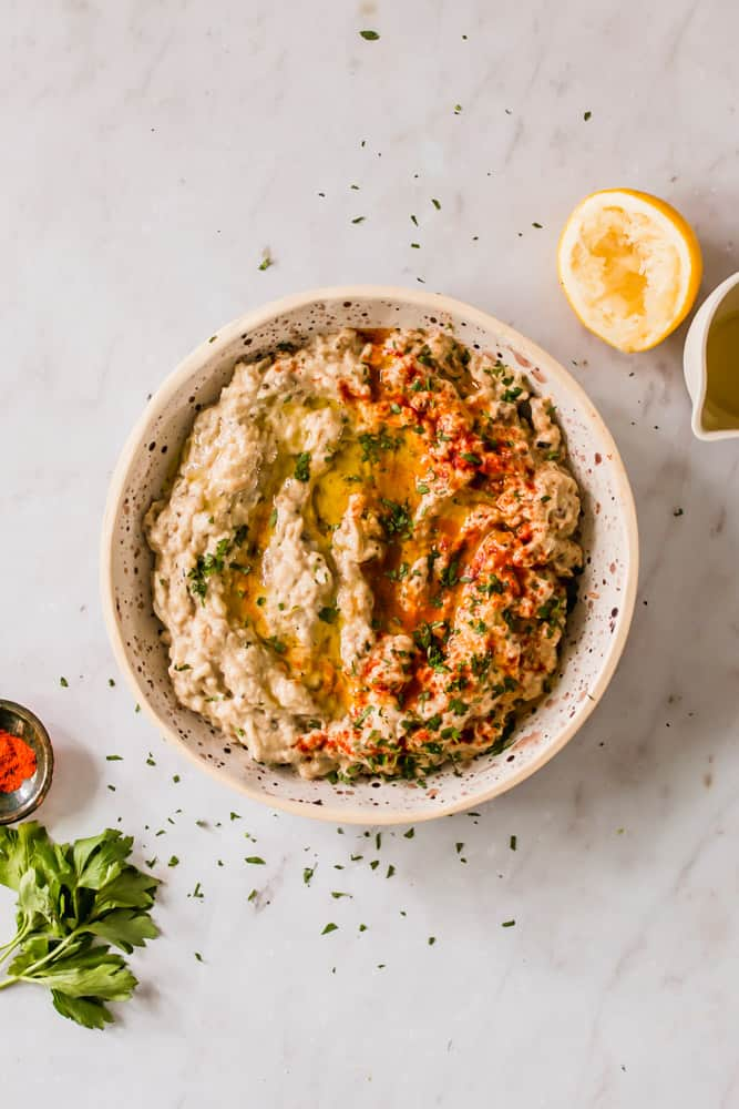 creamy white dip in a white bowl with oil, red spices, and green herbs on top.