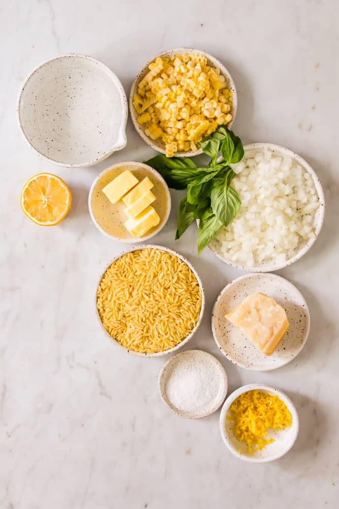 indidvidual white bowls holding corn, white onion, raw orzo pasta, cheese, butter, and lemon