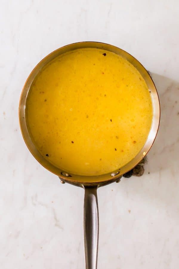 a yellow liquid in a metal pot