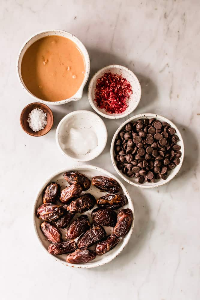 small white bowls filled with chocolate chips, peanut butter, strawberry powder, and dates.