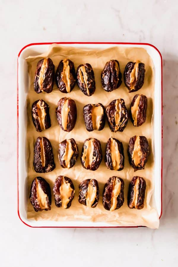 peanut butter stuffed dates in a white baking dish