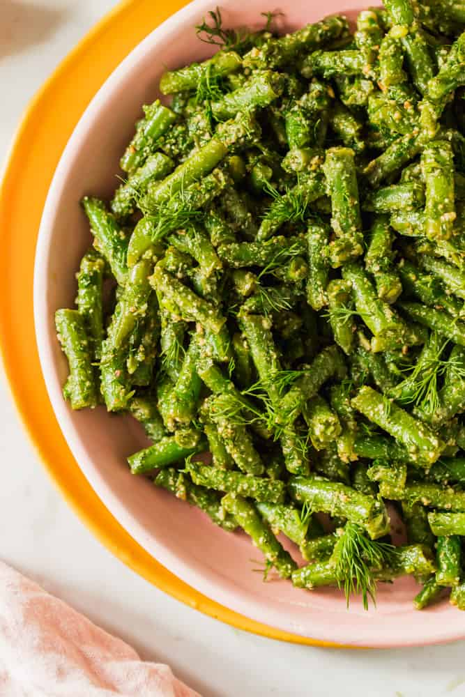 close up on cooked green beans tossed in pesto in a pink bowl