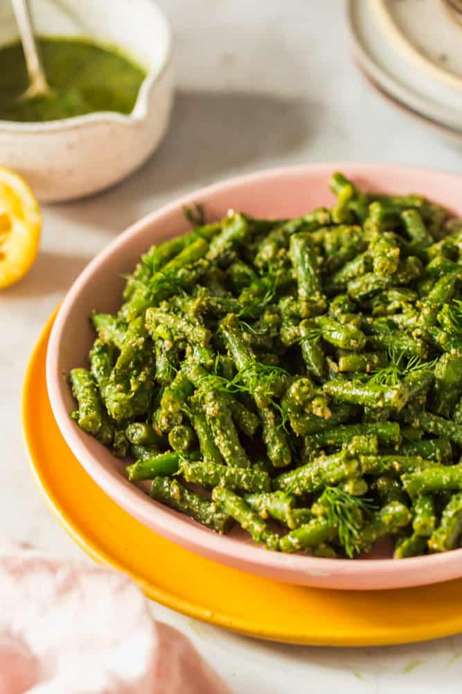 cooked green beans tossed in pesto in a pink bowl