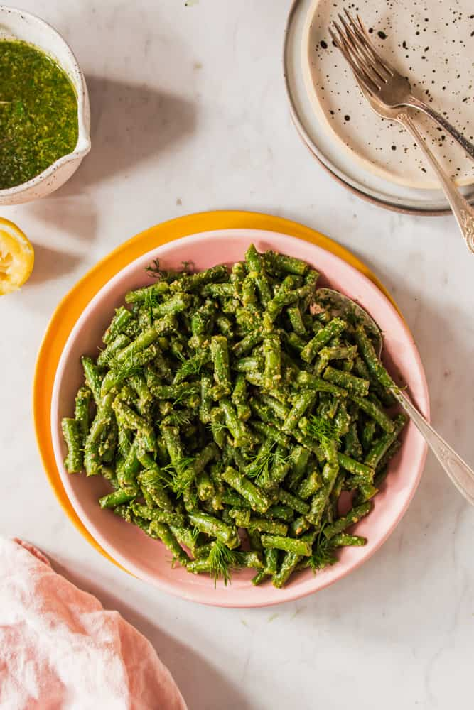overhead view of cooked green beans tossed in pesto in a pink bowl