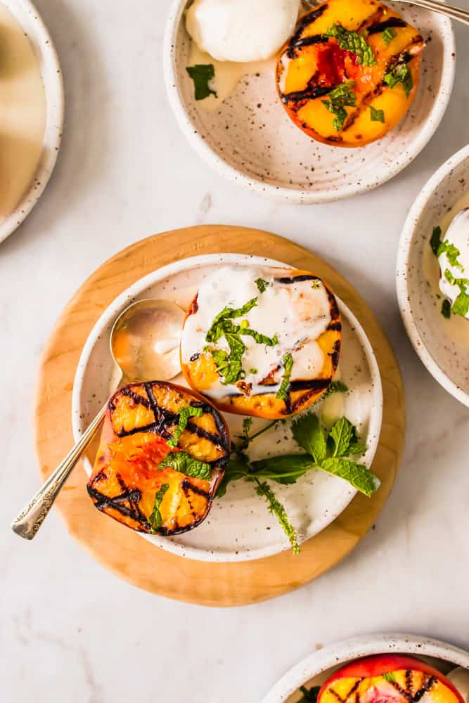 small white plates with grilled halved peaches, vanilla ice cream, and mint leaves