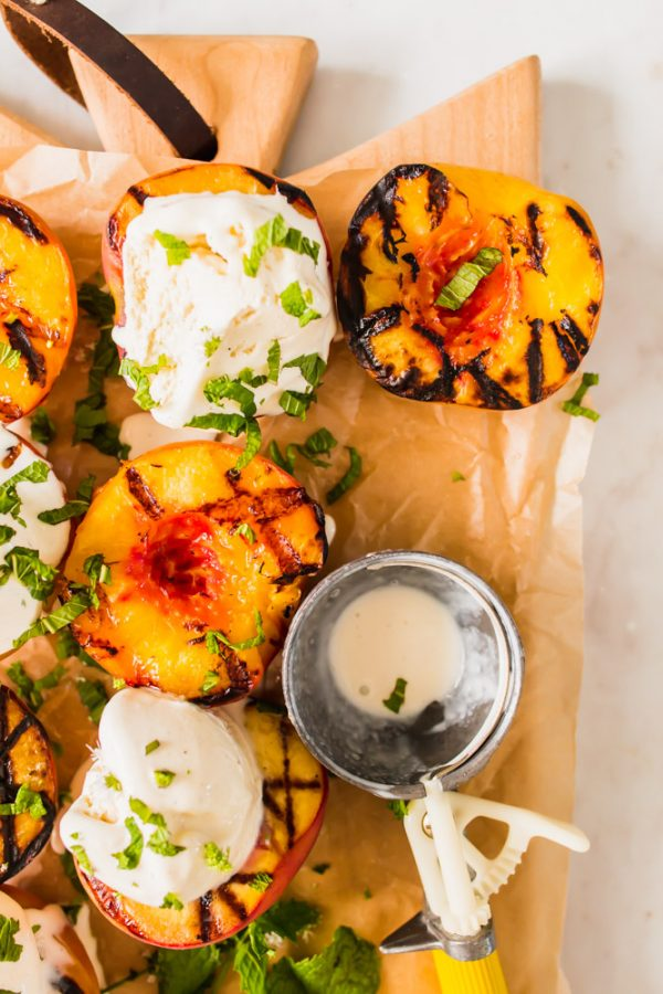 halved grilled peaches and vanilla ice cream on parchment paper