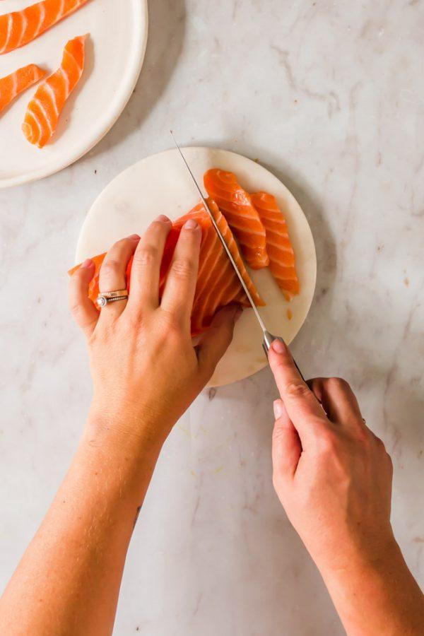 woman slicing raw salmon on a white cutting board