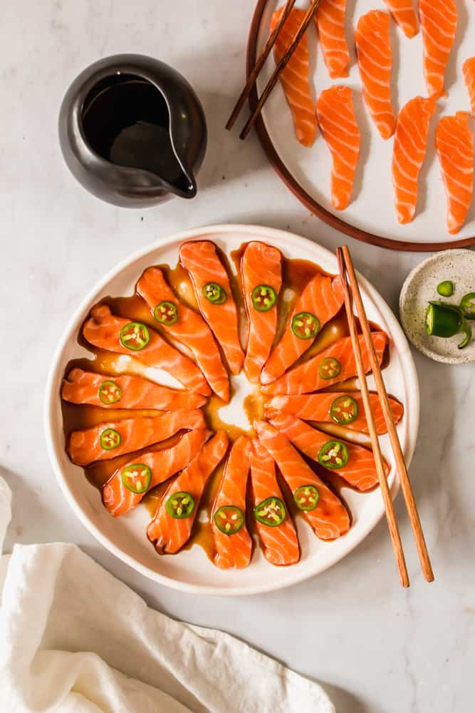 large white platter with sliced raw salmon, dark brown sauce, and jalapeno slices