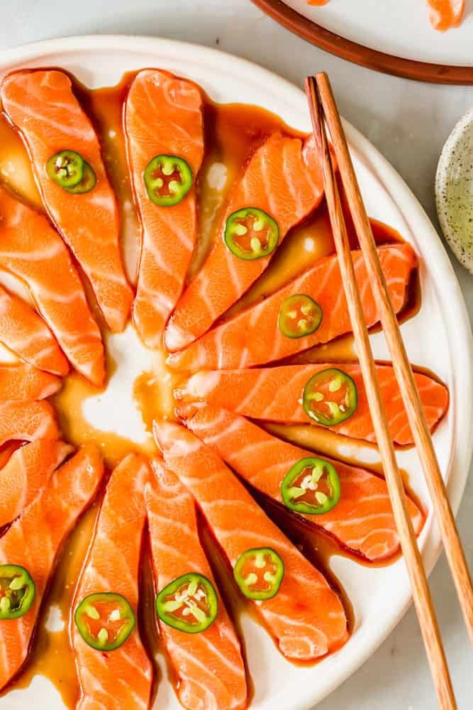 close up on a platter of raw salmon slices topped with brown sauce and jalapeno slices