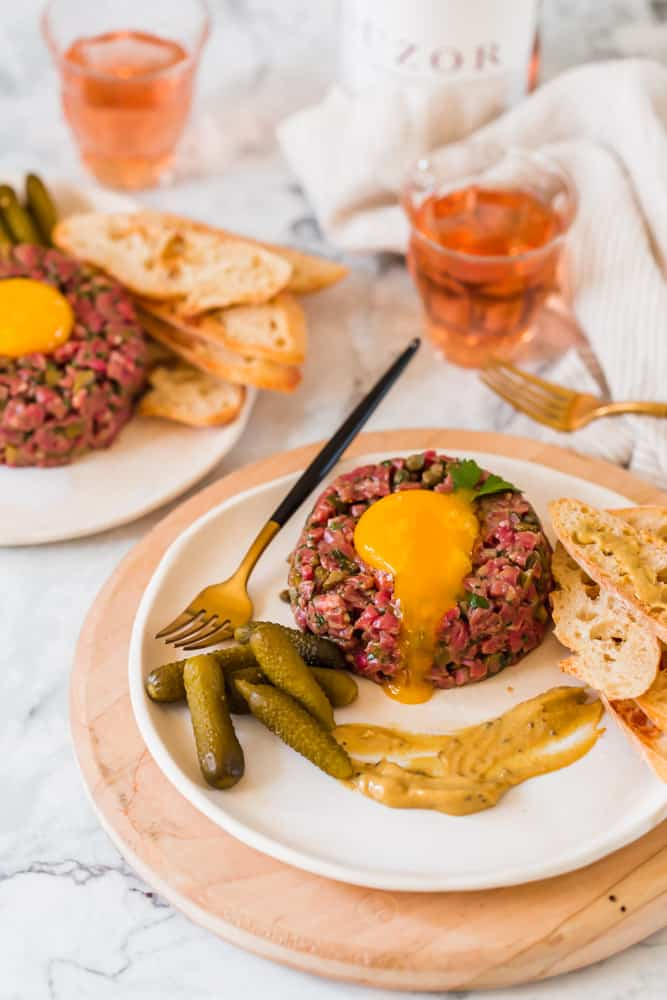 raw steak tartare on a white plate topped with an egg yolk and small pickles and bread on the side