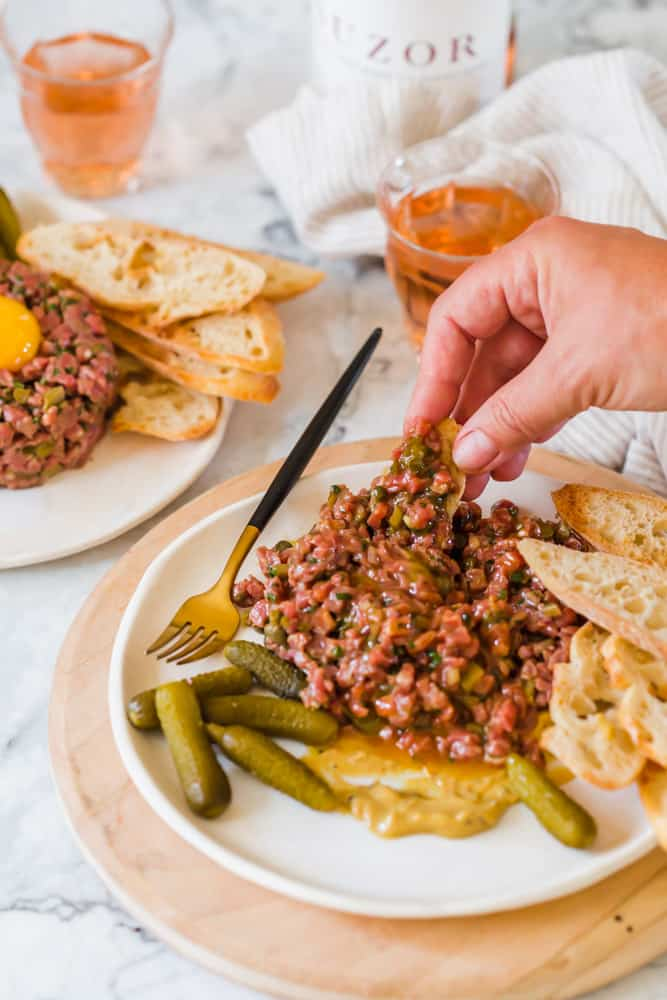 womans hand using bread to scoop steak tartare off of a white plate