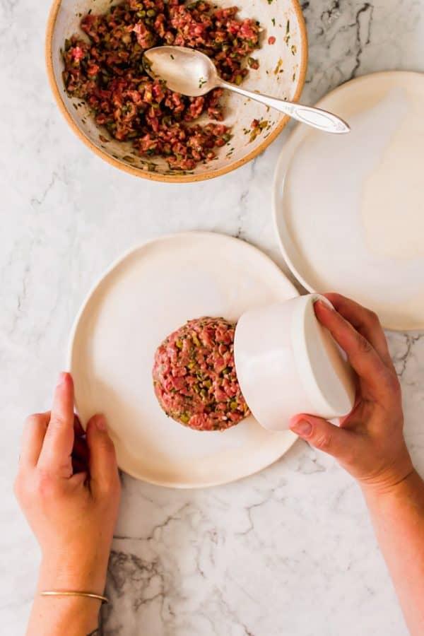 womans hands dumping a round piece of steak tartare from a white ramekin onto a white plate
