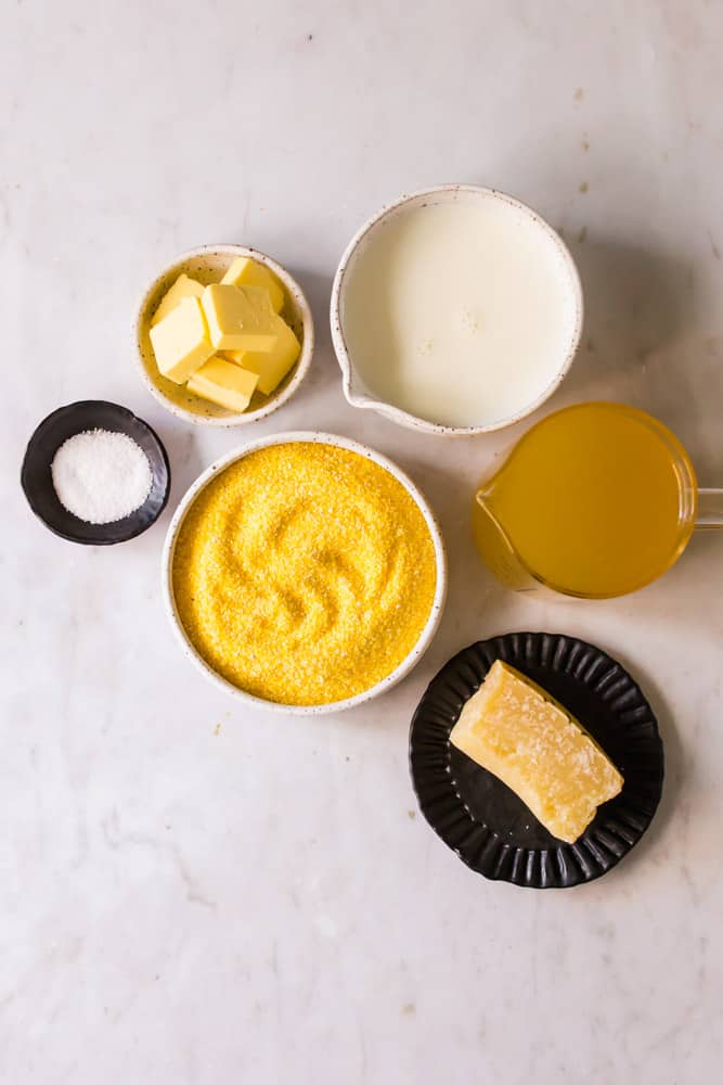 small white and black bowls filled with cornmeal, broth, milk, butter, and cheese.